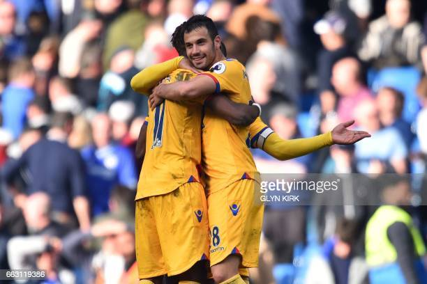 Crystal Palace's Serbian midfielder Luka Milivojevic and Crystal Palace's Ivorianborn English striker Wilfried Zaha embrace on the pitch at the final...