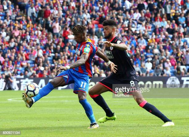 Crystal Palace's Wilfried Zaha holds of Huddersfield Town's Philip Billing during Premier League match between Crystal Palace and Huddersfield Town...