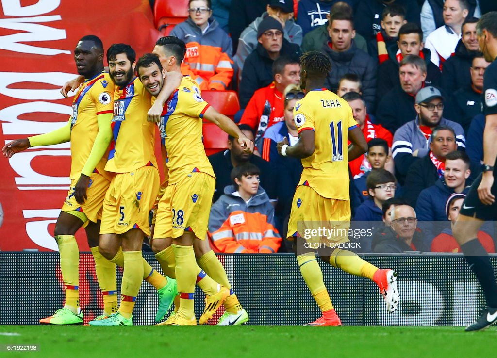 Crystal Palace's Zaire-born Belgian striker Christian Benteke (L) celebrates scoring a goal with Crystal Palace's English defender James Tomkins (2L) and Crystal Palace's Serbian midfielder Luka Milivojevic (3L) during the English Premier League football match between Liverpool and Crystal Palace at Anfield in Liverpool, north west England on April 23, 2017. / AFP PHOTO / Geoff CADDICK / RESTRICTED TO EDITORIAL USE. No use with unauthorized audio, video, data, fixture lists, club/league logos or 'live' services. Online in-match use limited to 75 images, no video emulation. No use in betting, games or single club/league/player publications. /