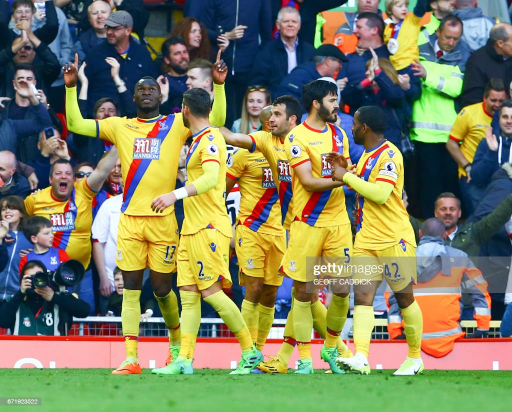 Crystal Palace's Zaire-born Belgian striker Christian Benteke (L) celebrates scoring a goal with Crystal Palace's English defender Joel Ward (2L), Crystal Palace's English defender James Tomkins (2R) and Crystal Palace's English midfielder Jason Puncheon (R) during the English Premier League football match between Liverpool and Crystal Palace at Anfield in Liverpool, north west England on April 23, 2017. / AFP PHOTO / Geoff CADDICK / RESTRICTED TO EDITORIAL USE. No use with unauthorized audio, video, data, fixture lists, club/league logos or 'live' services. Online in-match use limited to 75 images, no video emulation. No use in betting, games or single club/league/player publications. /