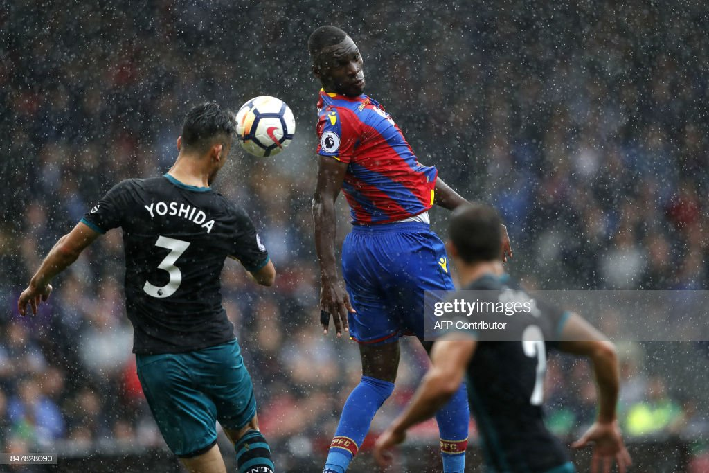 TOPSHOT - Crystal Palace's Zaire-born Belgian striker Christian Benteke (C) vies with Southampton's Japanese defender Maya Yoshida (L) during the English Premier League football match between Crystal Palace and Southampton at Selhurst Park in south London on September 16, 2017 / AFP PHOTO / Adrian DENNIS / RESTRICTED TO EDITORIAL USE. No use with unauthorized audio, video, data, fixture lists, club/league logos or 'live' services. Online in-match use limited to 75 images, no video emulation. No use in betting, games or single club/league/player publications. /