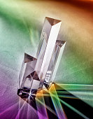 Crystal prisms photographed on tabletop with rainbow shadows.