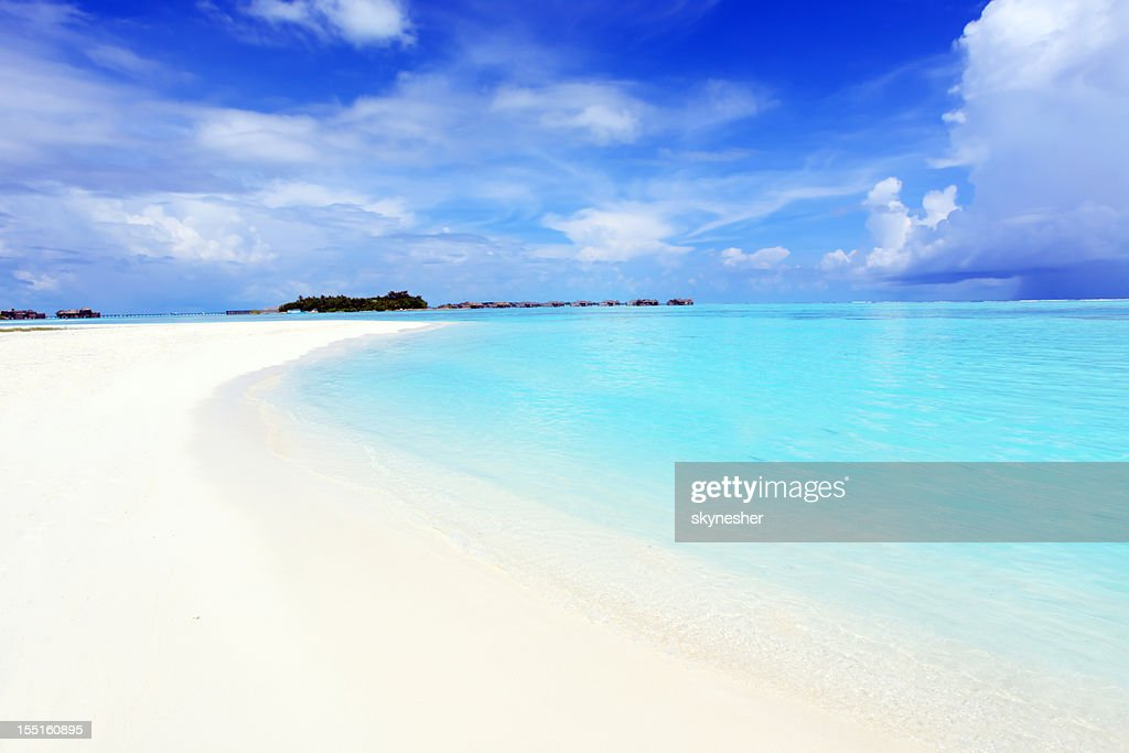 Crystal transparent sea and blue sky with white clouds. : Stock Photo