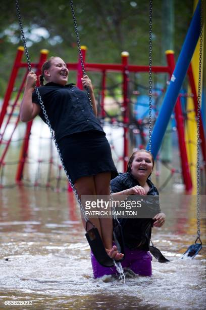 TOPSHOT Crystal Warner and Sharnia Johns play on playground equipment as floodwaters caused by Cyclone Debbie recede in the town of Beenleigh on...