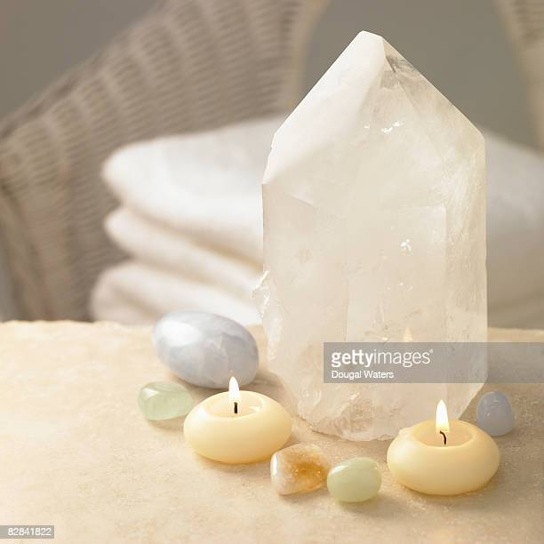 Crystals and lit candles close up.