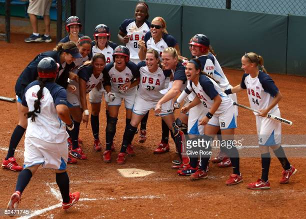 Crystl Bustos of the United States is greeted by her teammates at home plate as she scored on her 3run home run in the top of the ninth inning to...
