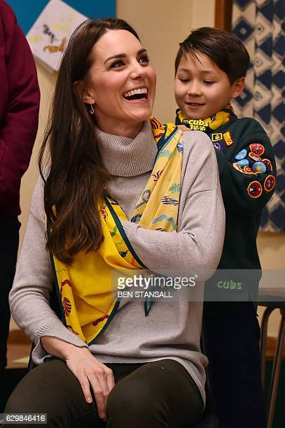 A cub scout uses a neckerchief to show Britain's Catherine Duchess of Cambridge how to support a broken arm during a Cub Scout Pack meeting with cubs...