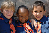 Three boys of diverse ethnic background in cub scout uniforms