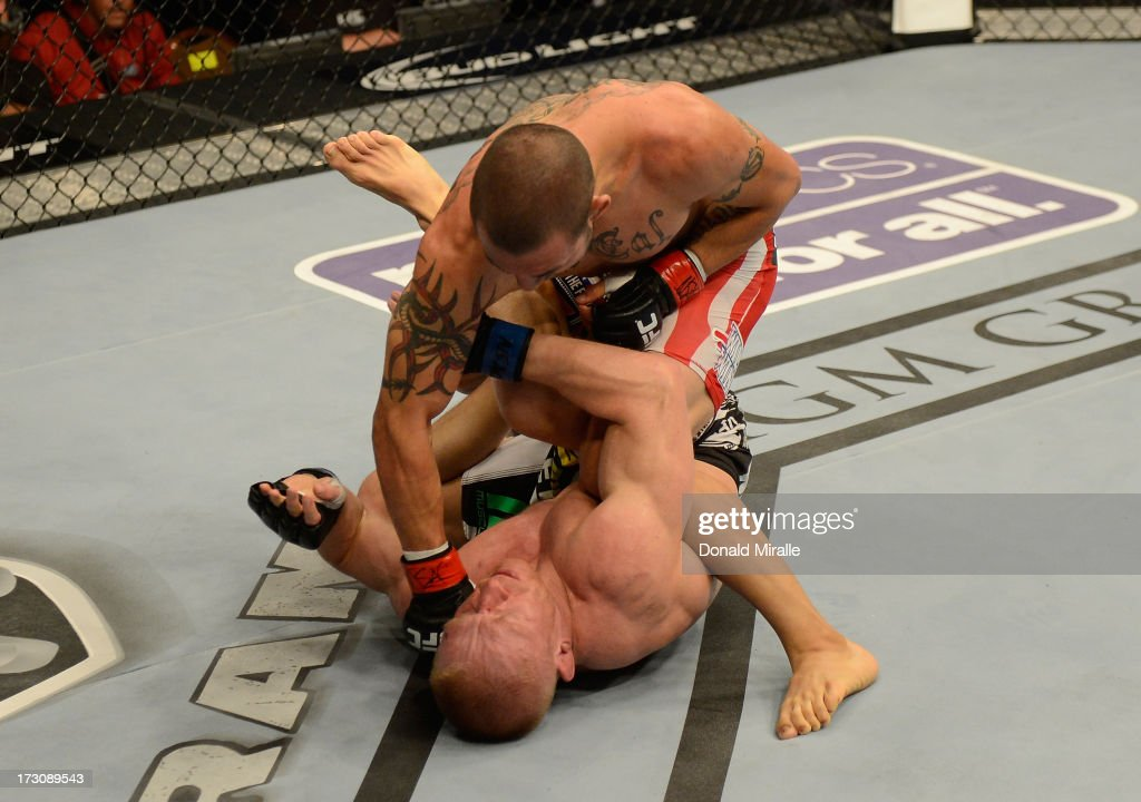 Cub Swanson (top) punches Dennis Siver in their featherweight fight during the UFC 162 event inside the MGM Grand Garden Arena on July 6, 2013 in Las Vegas, Nevada.