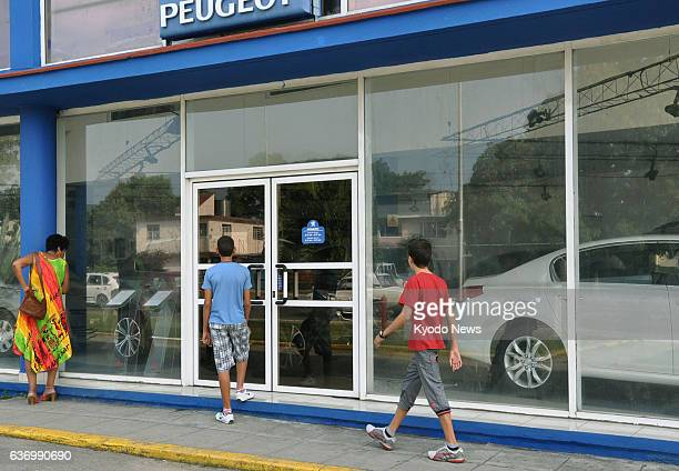 HAVANA Cuba A woman checks out the price tags of cars through the glass window of an automobile dealer in Havana in February 2014 following the Cuban...