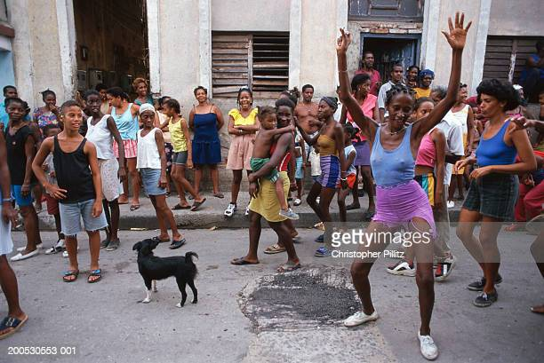 Cuba, girl dancing in street surrounded by crowd