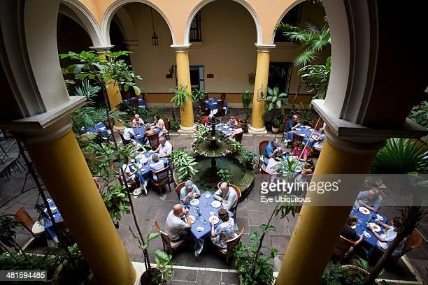 Cuba Havana Habana Vieja San Ignacio 54 Plaza de la Cathedral interior of the open air restaurant El Patio with people eating and drinking