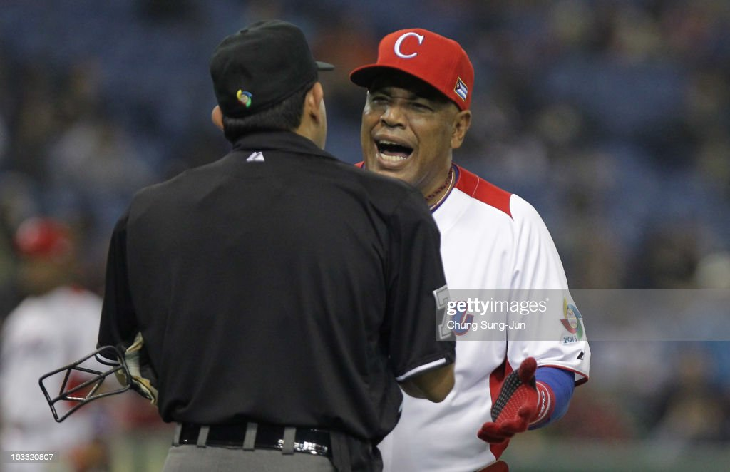 Cuba Head Coach Victor Mesa # 31 argues with home plate umpire Alfonso Marquez in the eighth inning during the World Baseball Classic Second Round Pool 1 game between the Netherlands and Cuba at Tokyo Dome on March 8, 2013 in Tokyo, Japan.