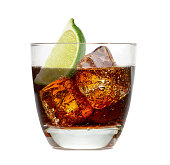 Cuba libre rum cocktail with ice cubes and lime wedge isolated on white background