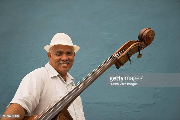 Cuba. Man carrying double bass.