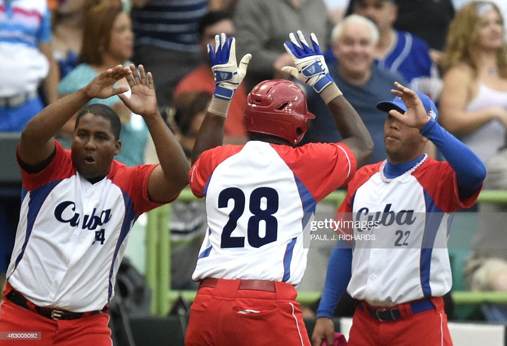 Cuba National baseball team infielder William Saavedra(28) receives high fives from teammates Alfredo Despaigne(54) and Yadiel Hernandez(22) after scoring in the second inning to make the game 2-0 against the Mexico National team in the final game of the Serie Del Caribe February 8,2015 in San Juan, Puerto Rico.