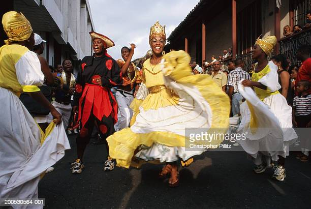 Cuba, performers dancing in street parade, smiling (blurred motion)