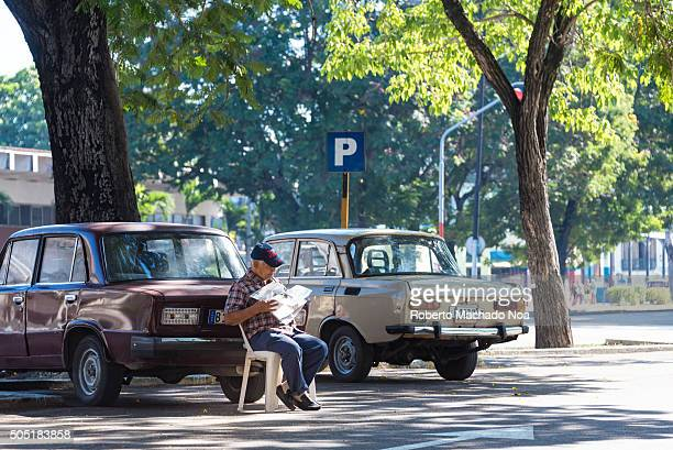 Cuba scenes Senior man incharge of car parking area sitting on a chair reading newspaper