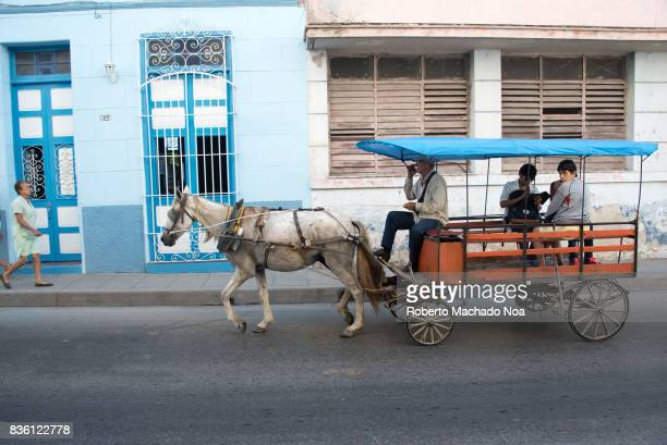Cuba transportation Horse drawn cart with two passengers passing from in front of white blue building