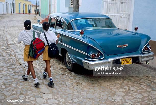 Cuba, Trinidad de Cuba, two school girls (10-11 years) walking on street, rear view