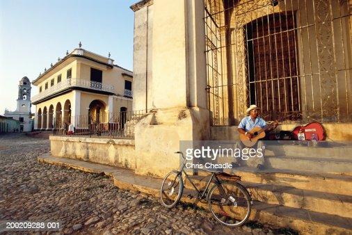 Cuba, Trinidad, man sitting on steps, playing guitar