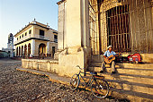 Cuba, Trinidad, man sitting on steps, playing guitar
