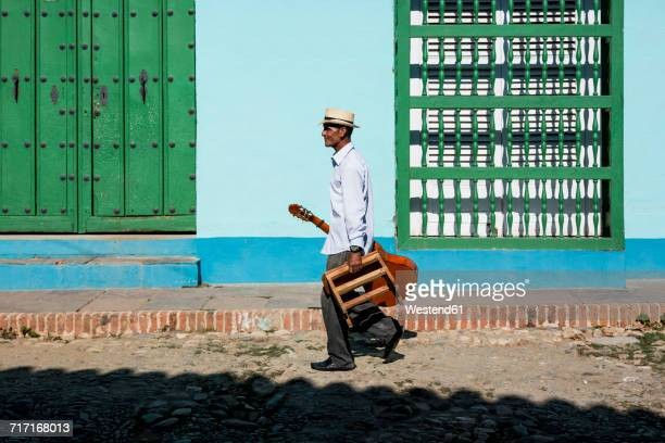 Cuba, Trinidad, walking man with guitar and stool on the street