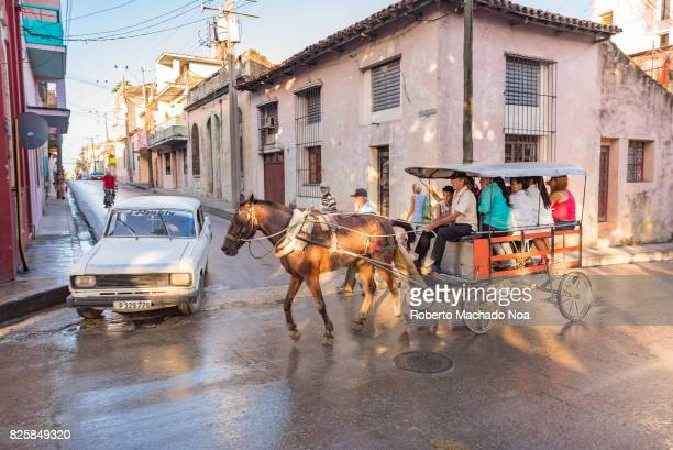 Cuba urban transportation Horse driven drawn cart full of passengers crossing an intersection in front of large old building and Moscovitch car...
