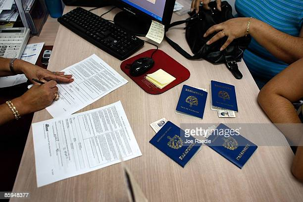 Cuban Americans show their Cuban passports as they purchase tickets to Cuba from a travel agent at Marazul Charters on April 13 2009 in Miami Florida...
