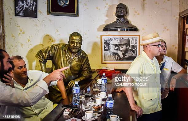 Cuban and US bartenders stand by a statue of US writer Ernest Hemingway at his favorite bar the Floridita in Havana on July 24 2015 A contest to find...