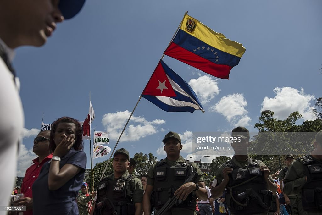 Cuban and Venezuelan flags are seen behind Army soldiers during a military parade for the 23rd anniversary of attempted coup of Hugo Chavez against...