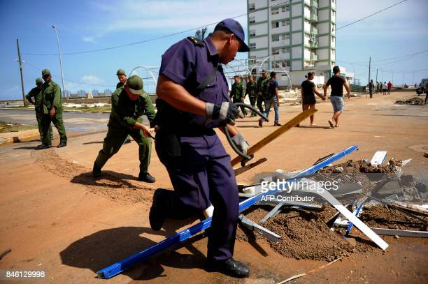 Cuban Army and Navy personnel collect debris during the cleanup ensuing the passage of Hurricane Irma in Havana on September 12 2017 / AFP PHOTO /...