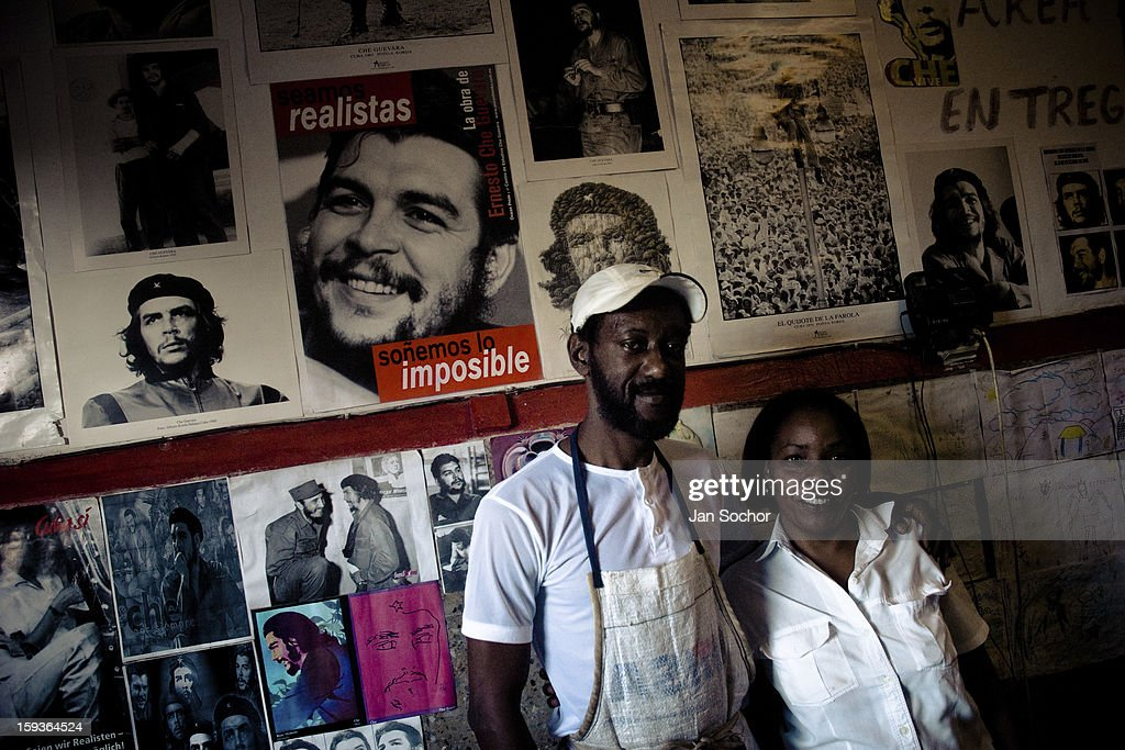 A Cuban bakery employees stand in front of a wall covered by pictures of the revolutionary leader Che Guevara, Alamar (the Eastern Havana), Cuba, on 12 February 2009 in Havana, Cuba. During the Cuban Revolution, an armed rebellion at the end of the 1950s, most of the revolutionary leaders started as unnamed soldiers fighting from the jungle. After taking over the power, they became autocratic rulers holding almost absolute power and pursuing the opposition. For some reason Cuban people never stopped to worship Fidel Castro, Che Guevara, Raul Castro and others. Cubans hang their photos and portraits on the wall at home, shops and working places even when they don't have to.