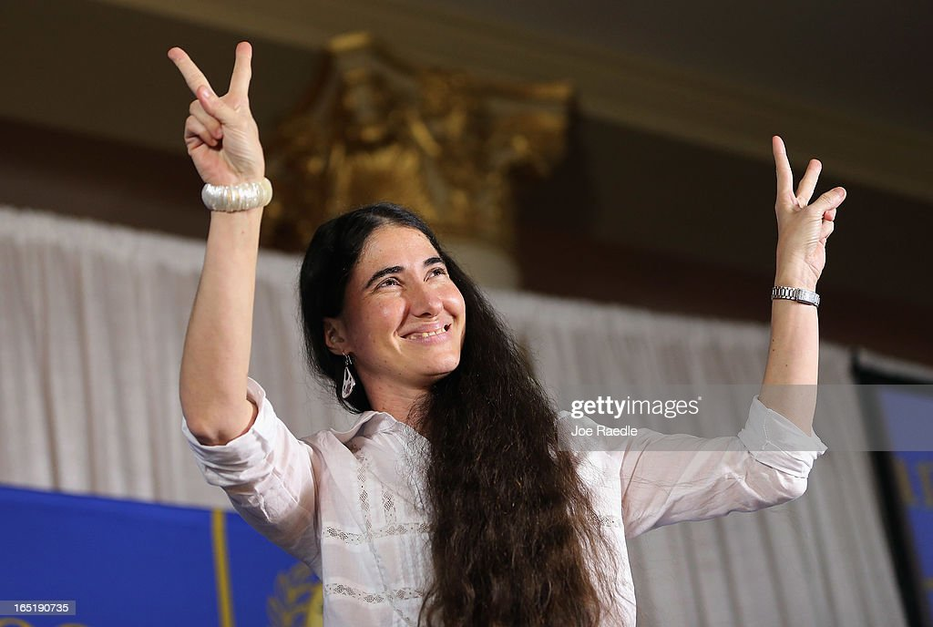 Cuban blogger and independent journalist Yoani Sanchez flashes the peace sign as she arrives to speak during an event at the Miami Dade College's Freedom Tower on April 1, 2013 in Miami, Florida. Sanchez's visit to Miami, the heart of the Cuban exile community, happens as she takes part in a world tour to speak about life in Cuba.