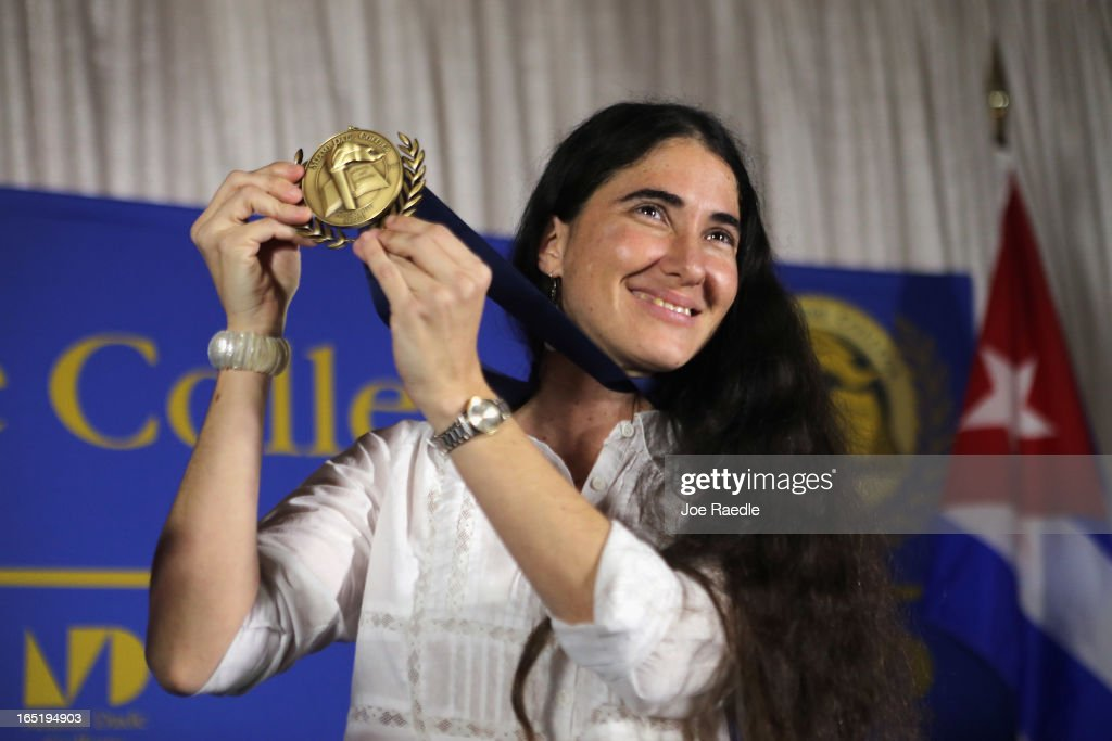 Cuban blogger and independent journalist Yoani Sanchez holds up a Presidential Medal of Miami Dade College given to her during an event at the Miami Dade College's Freedom Tower on April 1, 2013 in Miami, Florida. Ms. Sanchez visit to Miami, the heart of the Cuban exile community, happens as she takes part in a world tour to speak about life in Cuba.