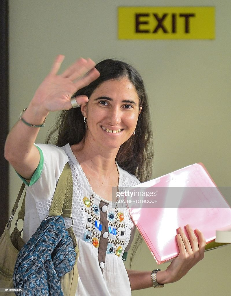 Cuban blogger Yoani Sanchez waves goodbye to her family upon departing from Havana's airport on February 17, 2013. Sanchez will visit Brazil, which will be her first stop on a foreign tour. During her stay in that country, the blogger will attend the opening of Brazilian filmmaker Dado Galvao's 2009 documentary 'Connection Cuba-Honduras,' in which she is interviewed. AFP PHOTO/ADALBERTO ROQUE
