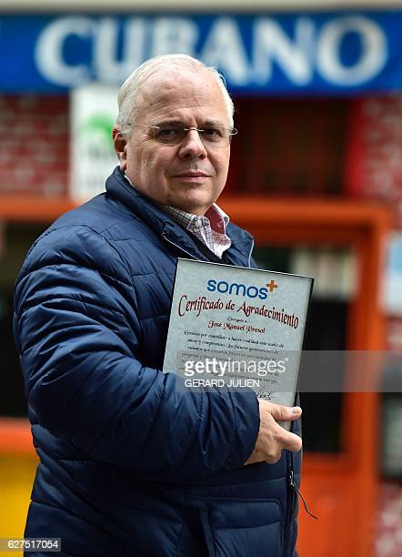 Cuban born Spanish retired economist Jose Manuel Presol poses with a certificate of gratefulness issued by the movement Somos in a central Madrid...