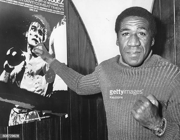 Cuban boxer Luis Manuel Rodriguez pictured punching a poster of rival and champion Nino Benvenuti prior to their upcoming fight at the Sport Palace...