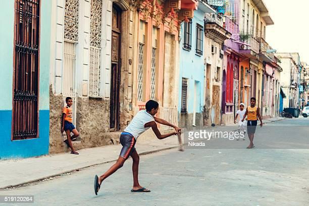 Cuban boys playing baseball in a empty street of Havana