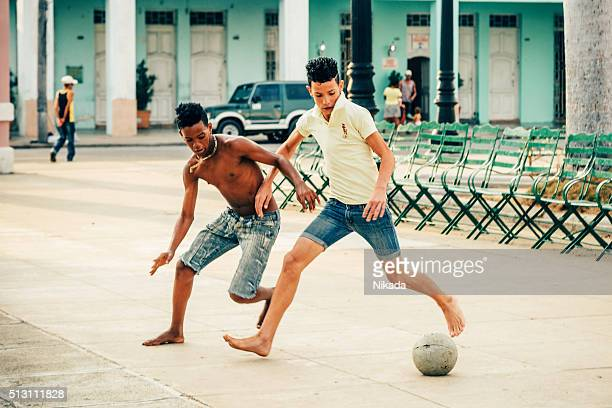 Cuban boys playing soccer in the street