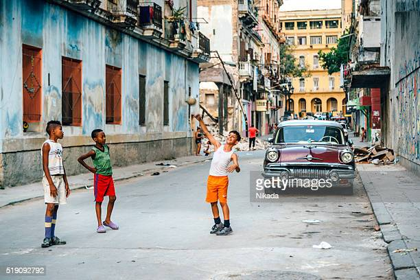 Cuban boys playing with ball on a street in Havana