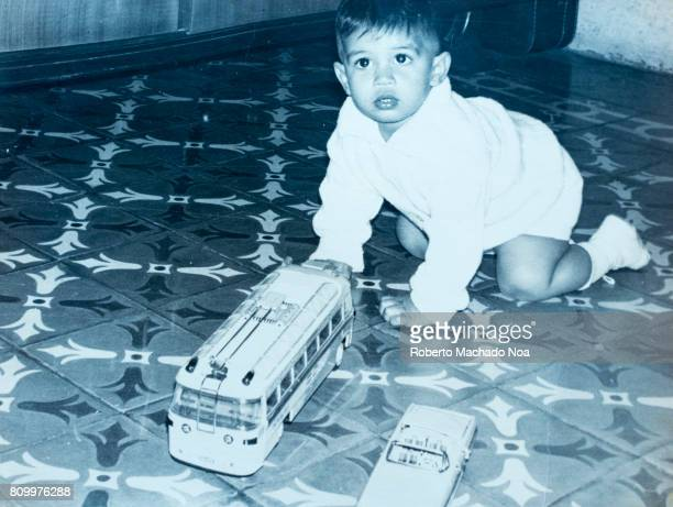 Cuban child boy lifestyles in 1968 Old black and white photograph of cute toddler playing with toy car and bus on tiled floor