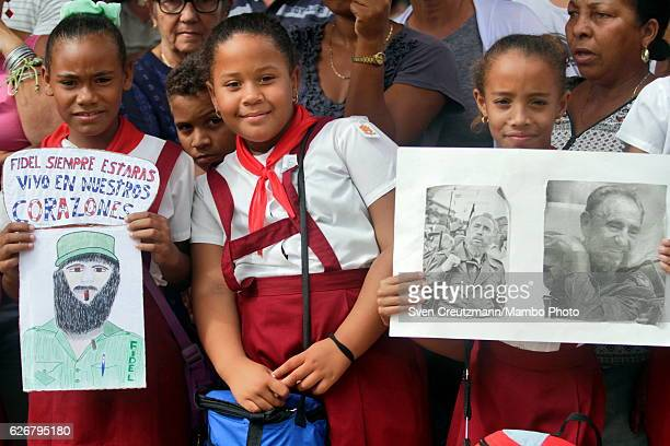 Cuban children hold a sign reading Fidel you will always be alive in our hearts as waiting for the caravan carrying the remains of former President...