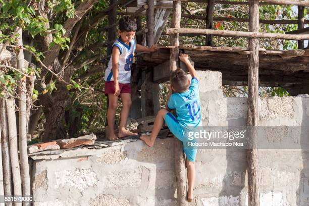 Cuban children looking for a lost baseball Two young boys climbing wooden log structure made above old grey cemented wall