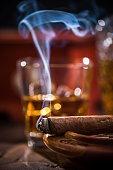 Cuban cigar smoke and luxurious Cognac in carafe.