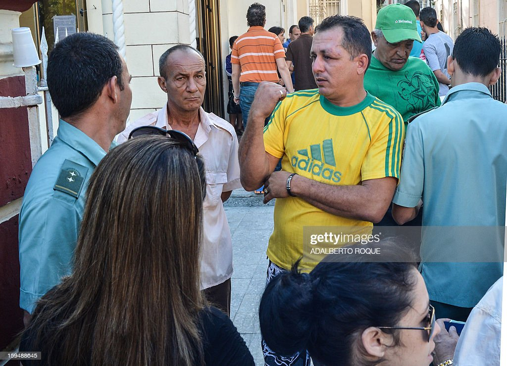 A Cuban citizen asks for information while queueing outside a Migrations Office to request new passport, on January 14, 2013 in Havana. A law allowing Cubans to travel abroad without special exit visas took effect on the communist-ruled island for the first time in half a century. The measure does away with the exit visas that have kept most Cubans from ever traveling abroad.