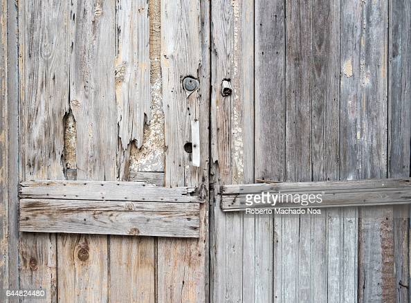 Cuban colonial architecture details Weathered unpainted wooden door entrance of a house Economic hardship has forced many people to keep their...