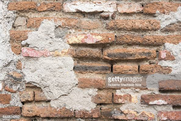 Cuban colonial weathered architecture details Brick wall in house facade Economic hardship has forced many people to keep their property without...