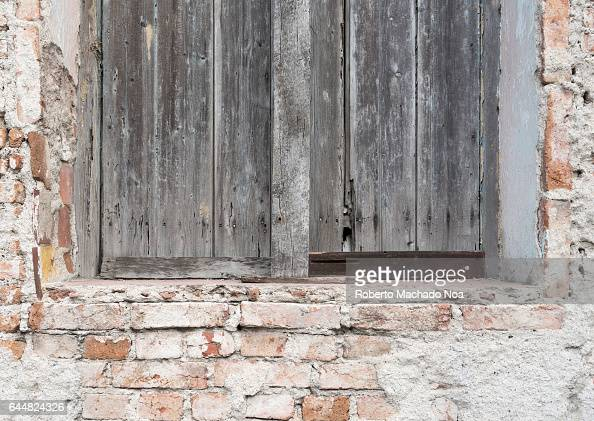 Cuban colonial weathered architecture details Wooden window and brick wall Economic hardship has forced many people to keep their property without...