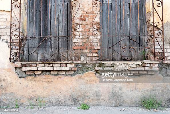 Cuban colonial weathered architecture details Wooden windows with iron guard in house facade Economic hardship has forced many people to keep their...